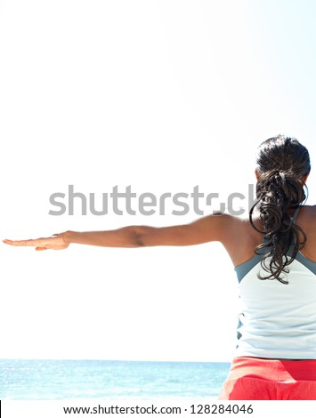 "Rear view of an ""african american"" woman stretching her arms to the sides while standing against a deep blue sky, exercising on a sunny day by the sea. - stock photo"