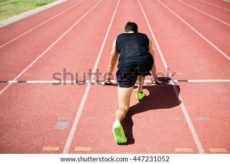 Rear view of an athlete ready to run on running track