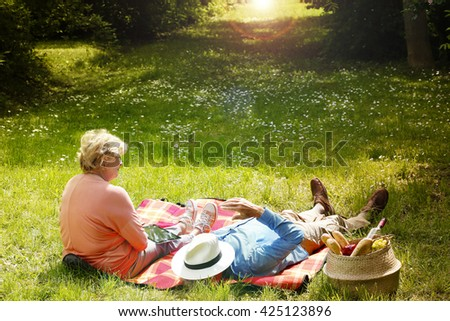 Rear view of an elderly woman sitting on blanket and senior man lying on grass while relaxing outdoor. - stock photo