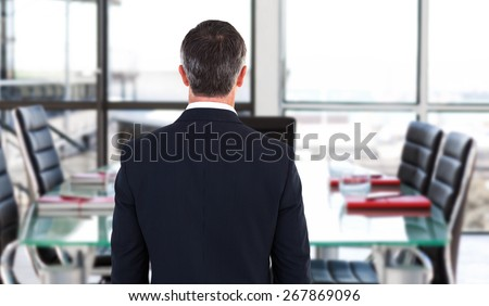 Rear view of an elegant businessman against empty corporate meeting room - stock photo