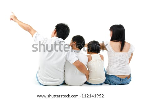 Rear view of Asian family looking at side, sitting on white background - stock photo
