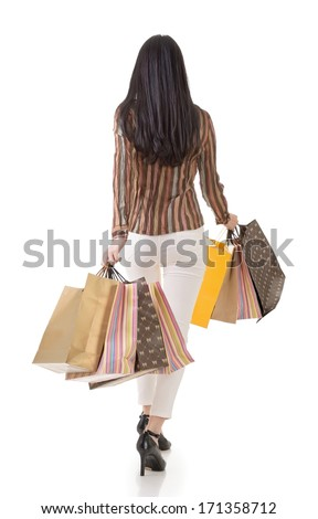 Rear view of Asian shopping woman holding bags, full length portrait isolated on white. - stock photo