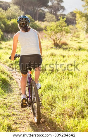 Rear view of athletic brunette mountain biking in the nature - stock photo