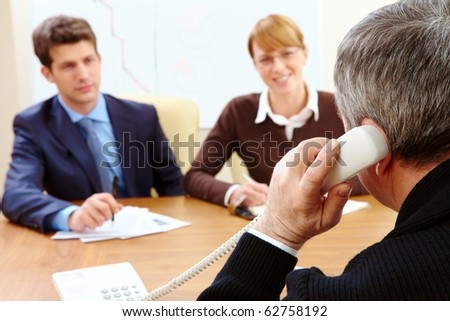 Rear view of bank employee calling on the phone opposite two visitors