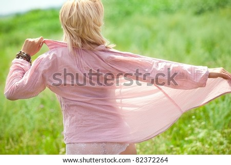 Rear view of beautiful woman undressing on field at summer sunset. - stock photo
