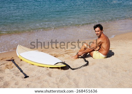Rear view of brunette hair man sitting on the beach while enjoying good sunny day, male surfer waiting for the big waves sitting on beautiful shoreline, man seat against sea - stock photo