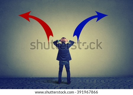 Rear view of business man standing in front of wall hands on head wondering which way to go. Full length businessman facing wall. Confused man looking at drawn arrow signs red and blue making decision - stock photo