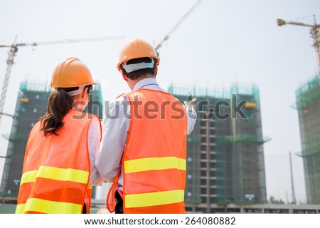 Rear view of business partners at the construction site - stock photo