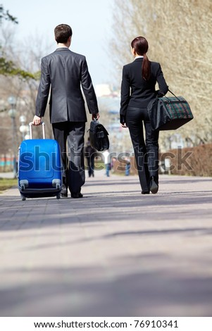 Rear view of business partners in suits walking with baggage - stock photo