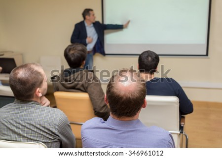 Rear view of business partners listening to lecturer and looking at whiteboard
