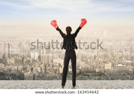 Rear view of business woman raising arms with boxing glove, full length.