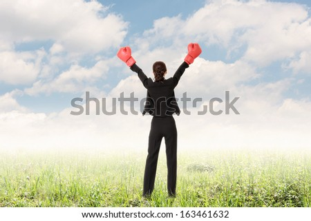 Rear view of business woman raising arms with boxing glove, full length. - stock photo