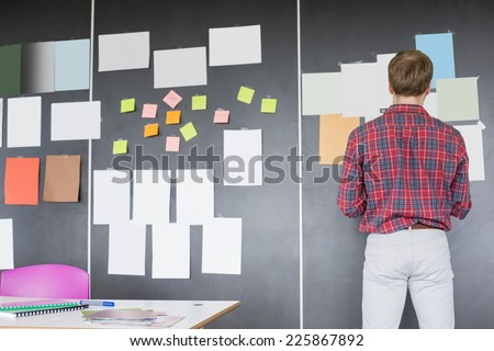 Rear view of businessman analyzing documents on wall at creative office - stock photo