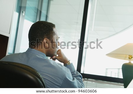 Rear view of businessman at desk - stock photo