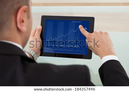 Rear view of businessman checking the stock market on digital tablet in office