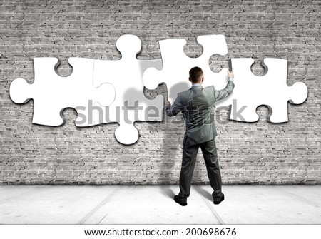 Rear view of businessman connecting white puzzle