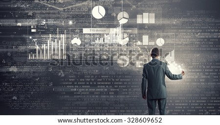 Rear view of businessman drawing marketing charts and graphs
