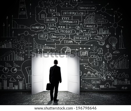 Rear view of businessman entering opened door in black wall - stock photo