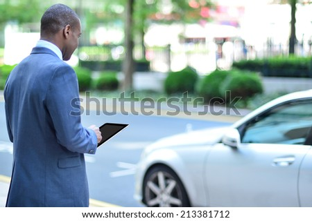 Rear view of businessman holding digital tablet  - stock photo