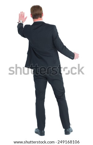 Rear view of businessman in suit gesturing on white background - stock photo