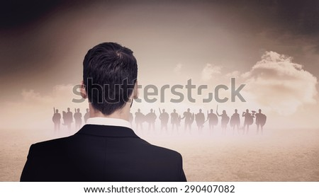 Rear view of businessman in suit standing against cloudy sky background - stock photo