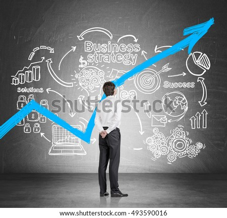 Rear view of businessman in white shirt examining startup sketch and blue graph on blackboard. Concept of prospective business career