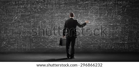 Rear view of businessman looking at chalk business sketches on wall - stock photo