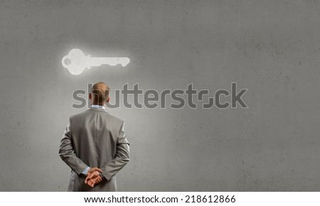 Rear view of businessman looking at key - stock photo