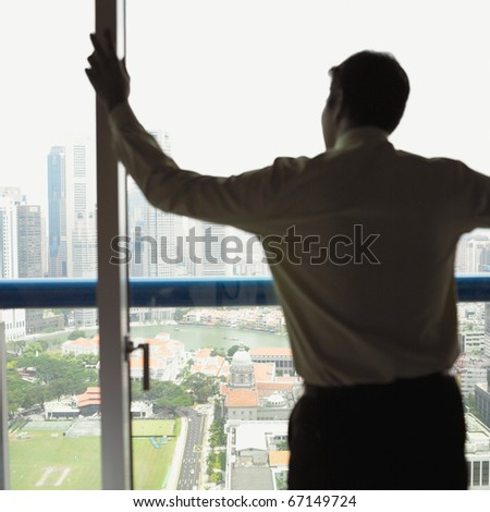 Rear view of businessman looking out office window - stock photo