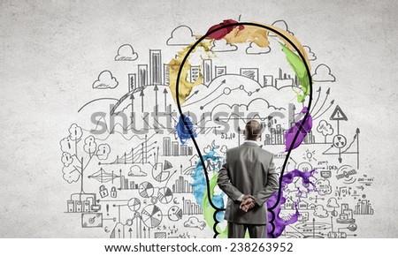 Rear view of businessman looking thoughtfully at business sketches - stock photo