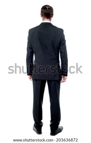 Rear view of businessman posing a wall  - stock photo