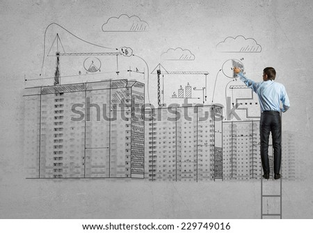 Rear view of businessman standing on ladder and drawing buildings - stock photo