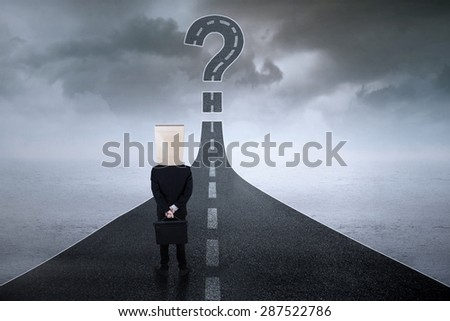 Rear view of businessman with cardboard head, standing on the road while looking at question mark - stock photo