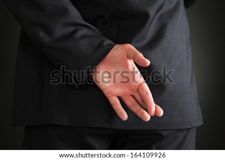 Rear View Of Businessman With Hands Behind Standing Over Black Background - stock photo