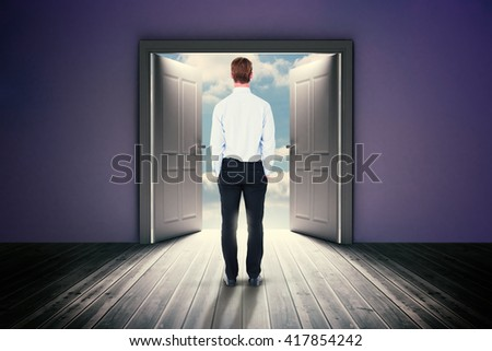 Rear view of businessman with hands in pockets against open big door on wall - stock photo