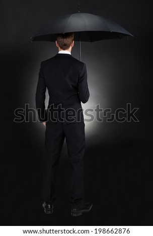 Rear view of businessman with umbrella against black background