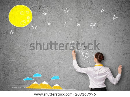 Rear view of businesswoman drawing rocket on wall