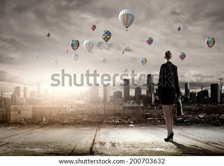 Rear view of businesswoman looking at aerostats flying above city - stock photo