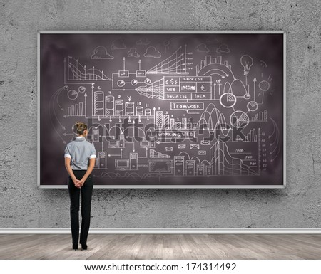 Rear view of businesswoman looking at chalkboard - stock photo