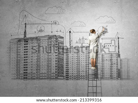 Rear view of businesswoman standing on ladder and drawing on wall - stock photo
