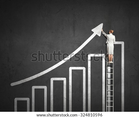 Rear view of businesswoman standing on ladder and touching top of arrow - stock photo