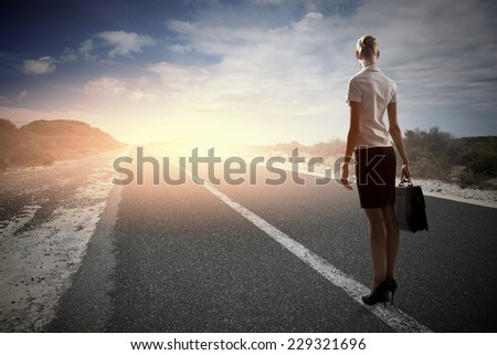 Rear view of businesswoman standing on road - stock photo
