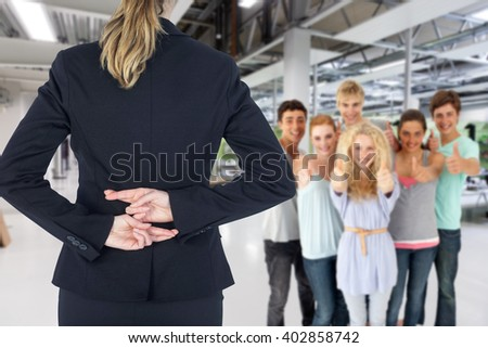 Rear view of businesswoman with fingers crossed behind her back against classroom - stock photo