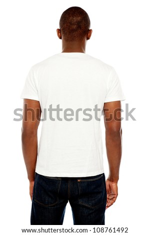 Rear view of casual young guy looking at white wall