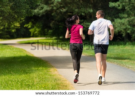 Rear view of Caucasian female and male runners outdoors - stock photo