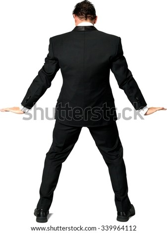 Rear view of Caucasian man with short black hair in a tuxedo holding invisible object - Isolated