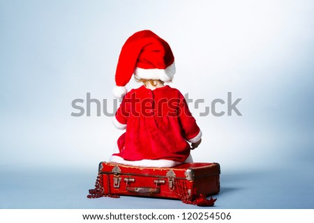 Rear view of child with Santa cap sitting on suitcase with gifts - stock photo