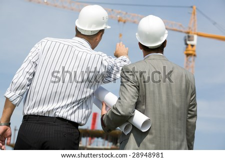Rear view of contractor pointing at crane with his colleague near by - stock photo
