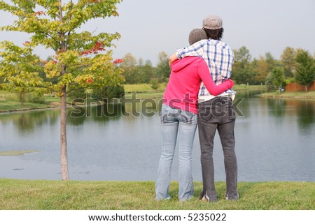 rear view of couple by a lake - stock photo