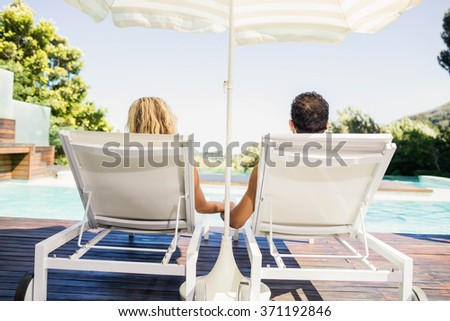 Rear view of couple on deck chairs poolside - stock photo